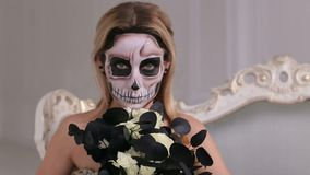 Girl in a dress with a bouquet of black flowers and makeup in form of a skeleton. A young blonde in a black dress with a bouquet of black flowers and makeup in stock video footage