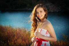 Girl in dress with a bouquet of smiles. Girl dress summer beauty hair sunset wind rays river smile bouquet look shoulders belt warm Royalty Free Stock Images