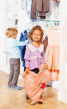 Girl with dress and boy behind chooses clothes Royalty Free Stock Photos