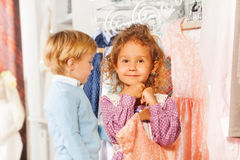 Girl with dress and boy behind choosing clothes Royalty Free Stock Image