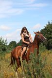 Girl in dress and brown horse portrait in forest Stock Image