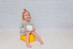 Girl in a dress, a child sitting on a yellow pot with toilet pap. A girl in a dress, a child sitting on a yellow pot with toilet paper in his hands royalty free stock photography