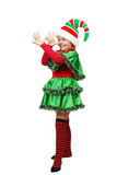Girl in a dress of the Christmas elf shows teasing. Isolated on a white background Royalty Free Stock Images