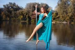 Girl dress dancing on a pole in the lake. Royalty Free Stock Photos