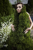 The girl in a dress from a decorative fur-tree. Stock Photography
