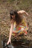 Girl in a dress in a dense forest. Among twigs Stock Image