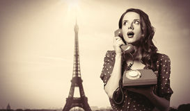 Girl in dress with dial phone. Surprised girl in polka dot dress with dial phone and Eiffel tower on background Stock Photo