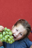 Girl with dress eating white grapes. Girl with blue dress eating a bunch of white grapes stock image