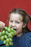 Girl with dress eating white grapes. Girl with dress eating a bunch of white grapes royalty free stock images