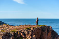 Girl in a dress on the edge of a cliff. Near the sea Royalty Free Stock Images