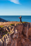 Girl in a dress on the edge of a cliff. Near the sea Royalty Free Stock Photos