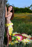 Girl in the dress of the firebird of flowers near the tree Royalty Free Stock Photography