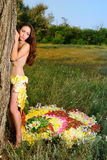 Girl in the dress of the firebird of flowers near the tree Stock Image
