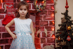 Girl in dress by the fireplace with the Christmas tree. Beautiful little girl in a red Christmas hat posing by the fireplace on Christmas Eve, enjoys gifts. A Stock Photos