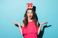 Girl in dress with a gift box on her head. Portrait of an excited brunette girl in dress with a gift box on her head isolated over blue background Royalty Free Stock Image