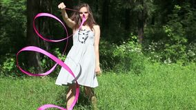 Girl in dress goes back to forest and twists pink ribbon. Pretty girl in dress goes back to forest and twists pink ribbon stock footage