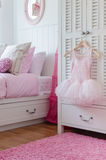 Girl dress hanging on wardrobe in bedroom Royalty Free Stock Photography