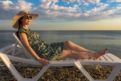 Girl in a dress and hat, enjoying the sunset lying on a chaise longue royalty free stock photography