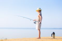 Girl in a dress and a hat with a fishing rod Stock Images