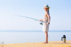 Girl in a dress and a hat with a fishing rod Royalty Free Stock Images