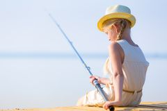 Girl in a dress and a hat with a fishing rod Stock Photo