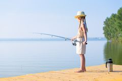 Girl in a dress and a hat with a fishing rod Stock Image