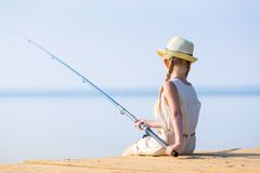 Girl in a dress and a hat with a fishing rod Royalty Free Stock Image