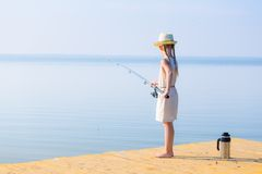 Girl in a dress and a hat with a fishing rod Royalty Free Stock Photography