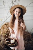 Girl in dress and hay hat keeping basket with little chick royalty free stock photos