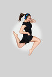 Girl in a dress with headphones jumping Stock Images