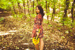 Girl in dress holding bunch of sunflowers in forest Stock Image