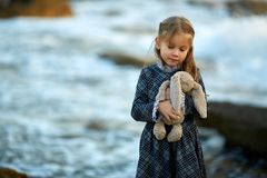 Girl in dress holding bunny toy in nature royalty free stock image