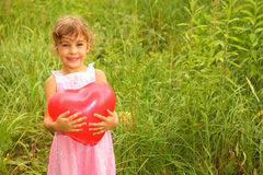 Girl in dress holding red balloon Stock Image