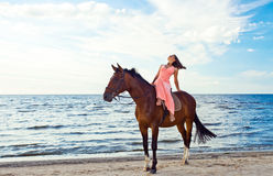 Girl in dress with horse on seacoast Stock Photography