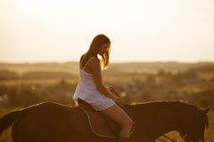 Girl in dress on a horse Stock Photo