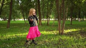 Girl in dress and jacket listening to music, park. Cute little blonde girl wearing a leather jacket and a pink dress listening to the music standing in a park on stock video footage