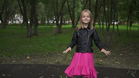 Girl in dress and jacket listening to music, park zoom out. Cute little blonde girl wearing a leather jacket and a pink dress listening to the music standing in stock video