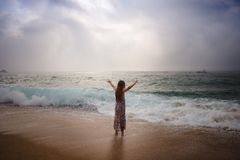 Girl with long hair standing by sea. Girl in dress and with long hair standing by sea. The waves are rolling. Girl raises hands Royalty Free Stock Image