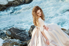 Girl in a dress in nature. Beautiful young girl in lush bride`s dress with hair and makeup on a background of spring nature near small river and forest Stock Photography