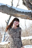 A girl in a dress near the old oak tree on the phone. Girl in leopard dress near the old oak tree, talking on the phone Royalty Free Stock Photos