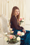 Girl in dress near the screen with flowers Royalty Free Stock Images
