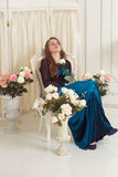 Girl in dress near the screen with flowers Royalty Free Stock Photos
