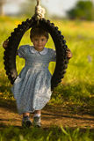 Girl in dress and old fashioned swing. Girl in dress gently swinging with nice green natural background Royalty Free Stock Image
