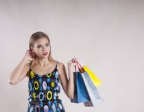 Beautiful girl in a dress with packages fashionable for purchases studio Stock Photography