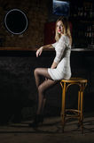 Girl in a dress and pantyhose sits in the bar Stock Image