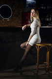 Girl in a dress and pantyhose sits in the bar Royalty Free Stock Image