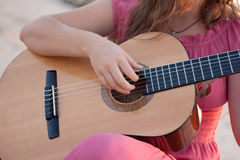 A girl in a dress playing a guitar. Shot on the nature Stock Photo