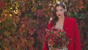 Girl in a dress and a red coat with a bouquet of flowers in an autumn Park. Portrait of a gorgeous girl in a dress and a red coat and with a bouquet of autumn stock footage