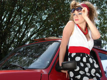 Girl in dress with red comapct car Stock Image