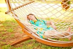 Girl in dress resting in a hammock Stock Image